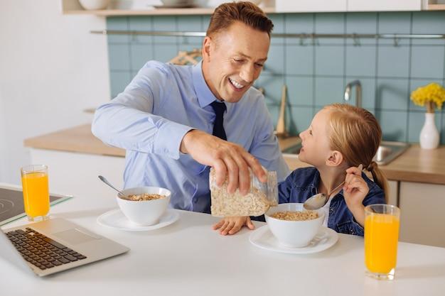 シリアルのあるバーを持って、彼女と一緒に朝食をとりながら娘のボウルにそれを追加して喜んでいる素敵な思いやりのある父親