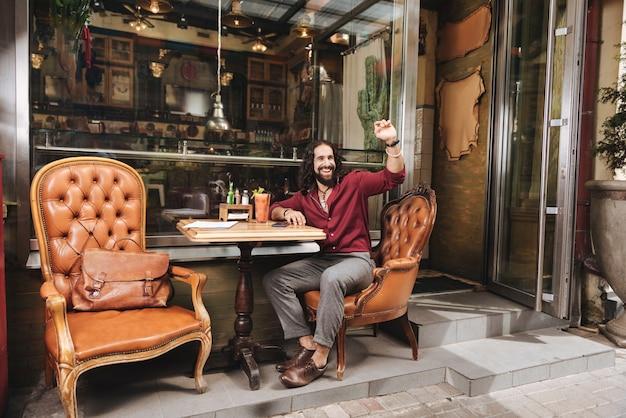 Довольный симпатичный мужчина смотрит на официанта, сидя за столиком в кафе
