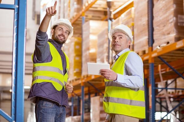 Довольный хороший человек, стоящий вместе со своим коллегой, показывая свое хранилище на складе