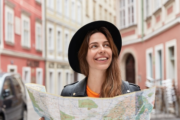 Delighted optimistic female toursit finds place on map, walks in city center during summer trip, wears stylish black hat, poses against urban setting