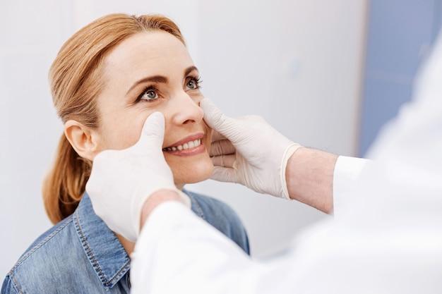 긍정적 인 분위기에있는 동안 그녀의 의사를보고 웃고 기쁘게 즐거운 좋은 여자