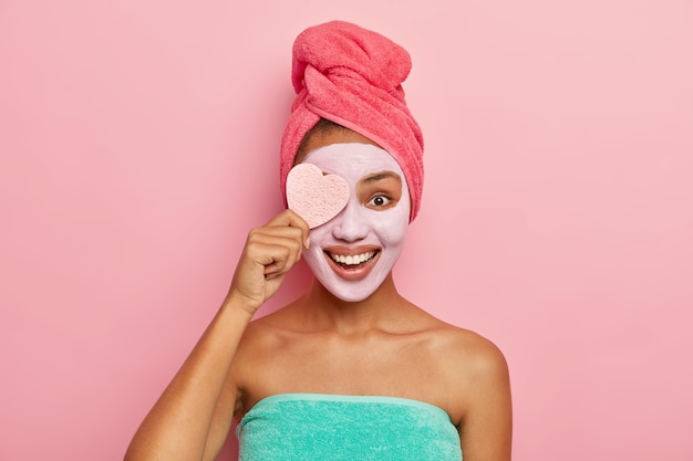 Delighted pleased female model holds cosmetic sponge, applies facial clay mask which suits her skin, has cosmetic procedures in bathroom