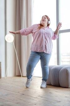 Довольно полная женщина танцует дома, наслаждаясь своей музыкой