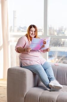 소파에 앉아있는 동안 아름다움에 대해 읽고 기쁘게 통통한 여자