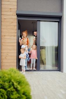 Радостная позитивная семья, стоящая у двери