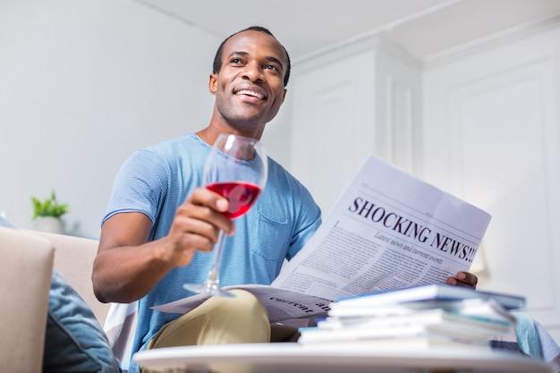 Радостный позитивный радостный мужчина улыбается и держит бокал вина, отдыхая дома