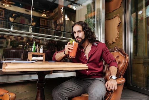 Довольный позитивный мужчина, наслаждаясь коктейлем, находясь в кафе