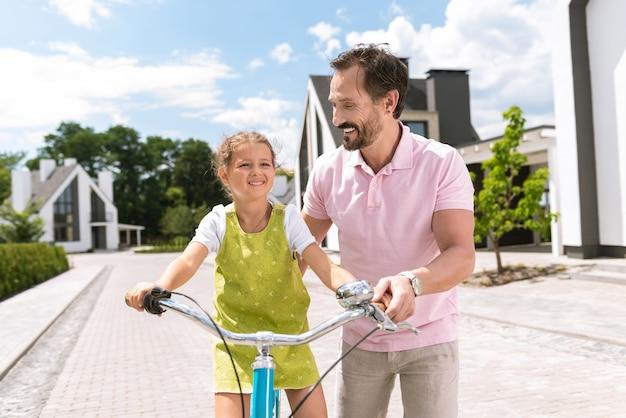 그녀가 자전거를 타도록 돕는 동안 그의 딸을보고 기쁘게 긍정적 인 남자