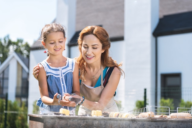 Delighted positive woman helping her daughter while grilling meal together