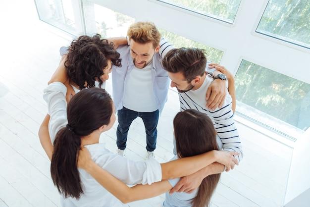 Приятные позитивные молодые люди стоят в кругу и разговаривают друг с другом, сохраняя командный дух.