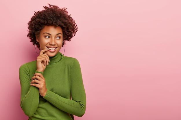 빛나는 곱슬 머리를 가진 기쁘게 예쁜 여성, 넓게 미소 짓고 하얀 이빨을 보여주고 입 근처에 손을 대고 캐주얼 녹색 터틀넥을 입고 옆으로 보이며 분홍색 벽에 고립 된 빈 공간