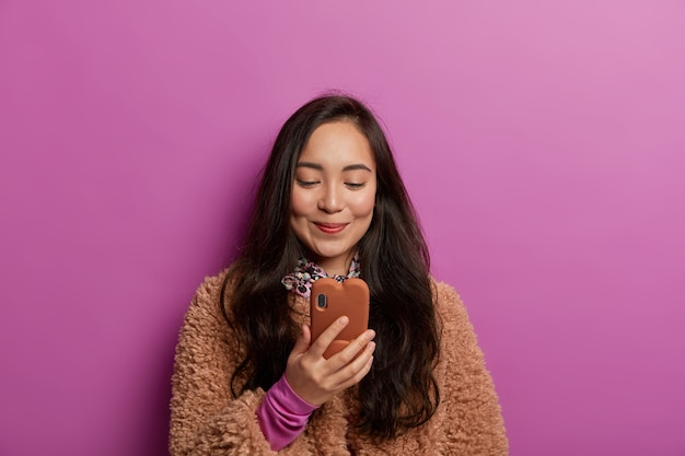 Delighted pretty young asian woman with dark hair, reads interesting news, has gadget addiction, pleased to receive message, dressed in brown coat