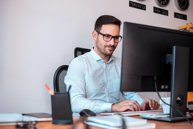 Обрадованный программист в очках пользуется компьютером.