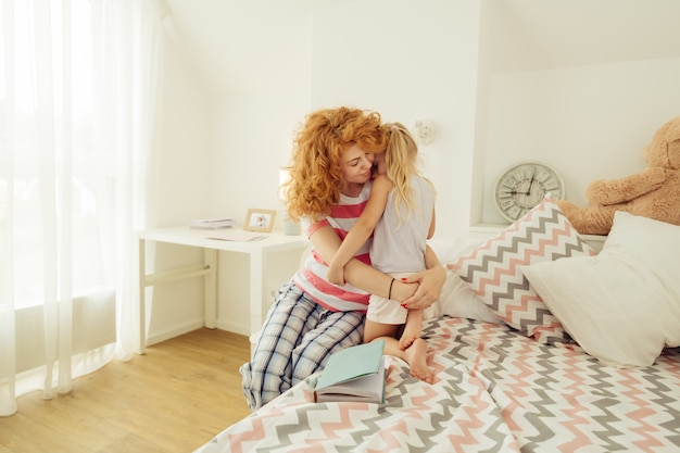 Delighted red haired woman hugging her daughter