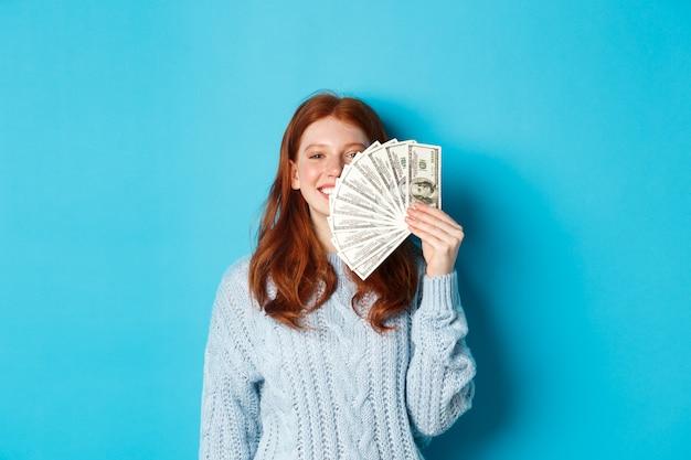 顔の近くにお金を見せて、満足して笑って、青い背景の上で買い物の準備ができて立っている喜んで赤毛の女性。