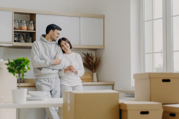 喜んでリラックスした夫と妻は、モダンなキッチン家具の近くでポーズをとり、移動式の日には段ボール箱に囲まれた表情を持ち、テイクアウトコーヒーを飲みます。抵当。