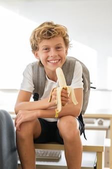 Довольный школьник ест банан в классе