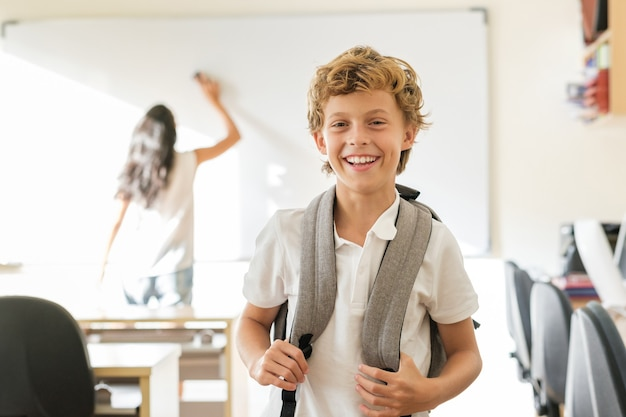 Delighted schoolboy standing in classroom with blurred teacher