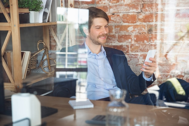 Delighted scrolling phone, chatting. young man, manager return to work in his office after quarantine, feels happy and inspired. coming back to normal life. business, finance, emotions concept.