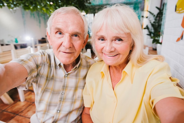 Delighted senior couple hugging sitting in cafe and shooting selfie