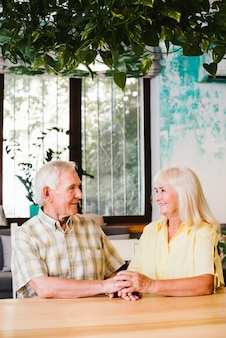 Delighted senior couple sitting in cafe and holding hands