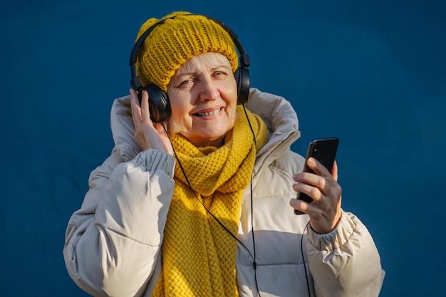 음악을 듣고 스마트폰을 사용하는 기뻐하는 시니어 여성