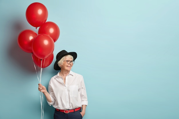 Delighted smiling lady has wrinkled skin, has party at work with colleagues, celebrates retirement, holds red air balloons, wears fashionable clothes, isolated over blue wall with blank space