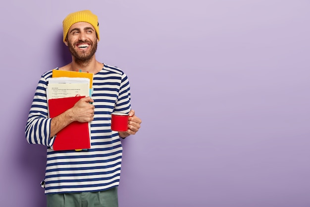 Delighted unshaven young man student holds papers and red notepad, holds cup with hot drink, has coffee break, being in good mood, looks aside with broad smile, isolated over purple background