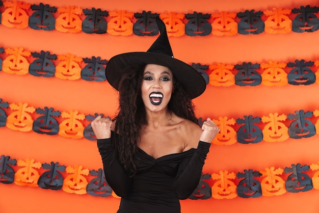 Delighted witch woman in black halloween costume screaming as winner isolated over orange pumpkin wall