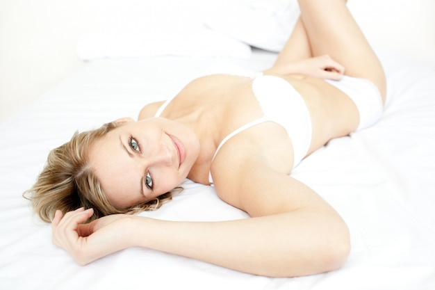 Delighted woman relaxing lying on her bed