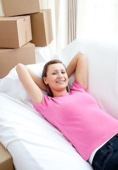 ボックスでソファでリラックスしている喜んでいる女性