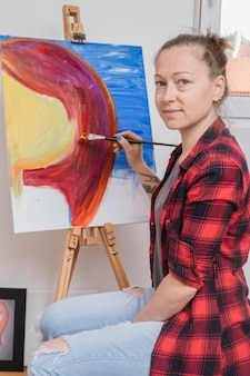 Delighted woman sitting by easel and looking at camera