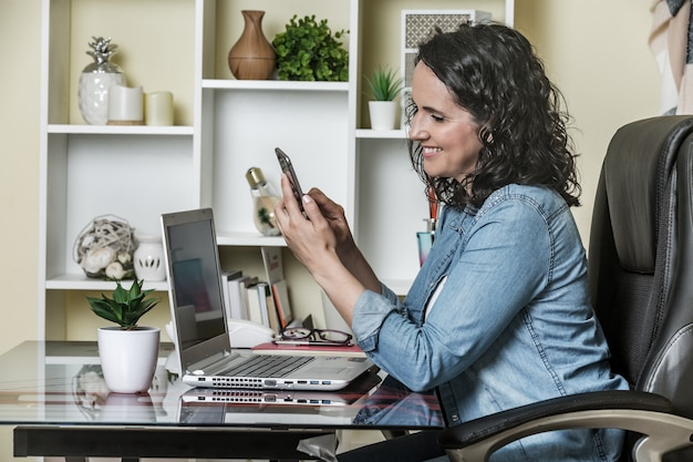 Delighted woman using smartphone with interest while sitting at desk with laptop at home