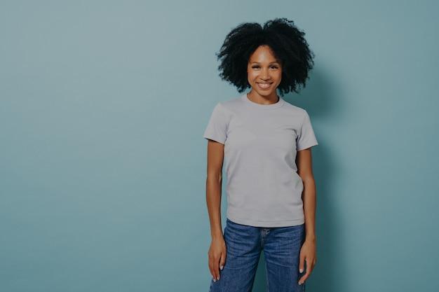 青い背景の上に心地よい笑顔で孤立し、カジュアルな白いtシャツとジーンズを着て、気分が良く、前向きな姿勢を示している、喜んでいる若いアフリカの女性。幸せな混血の女性