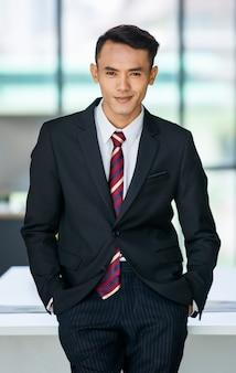 オフィスのポケットに手を入れて立ってカメラを見てフォーマルなスーツを着て喜んで若いアジアの民族男性起業家