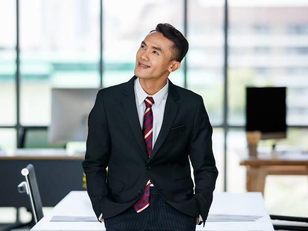 幸せそうな顔とオフィスで自信を持って立っているフォーマルなスーツを着て喜んでいる若いアジアの民族男性起業家。