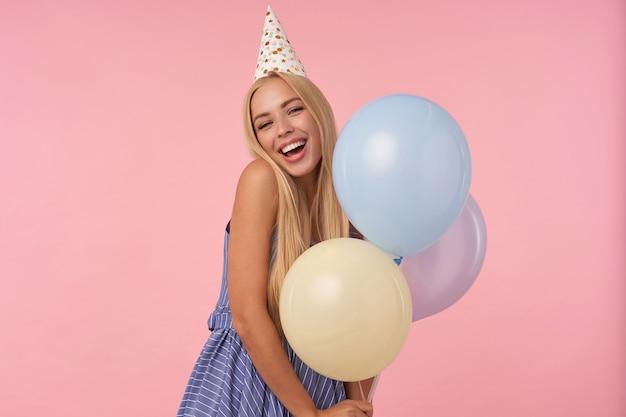 Восторженная молодая блондинка радуется, позируя в разноцветных воздушных шарах, в праздничной одежде и шляпе-конусе, изолированной на розовом фоне, демонстрируя свои приятные эмоции