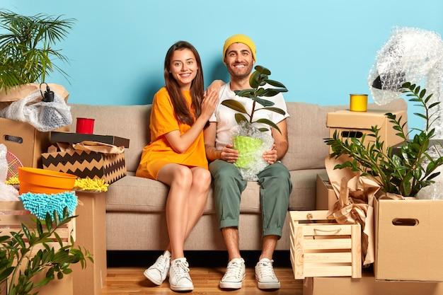 Довольная молодая пара сидит на диване в окружении коробок