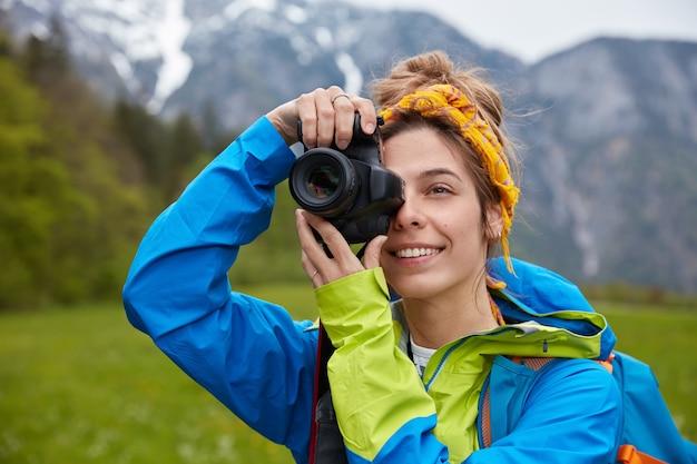 Felice giovane donna europea scatta foto durante un'escursione, tiene la macchina fotografica professionale