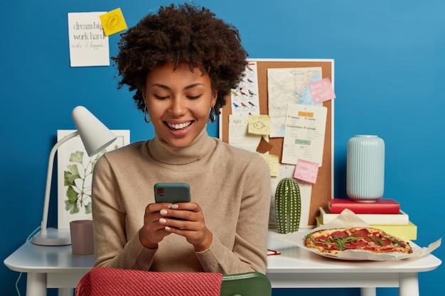 곱슬 헤어 스타일을 가진 기쁘게 젊은 여성 모델은 채팅 및 인터넷 서핑을 위해 휴대 전화를 사용하고 작업을 마친 후 여가 시간을 즐깁니다.