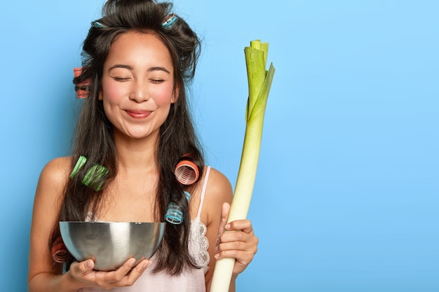 Delighted young female model with hair curlers, carries green leek and bowl, makes salad of healthy ingredients, keeps eyes shut