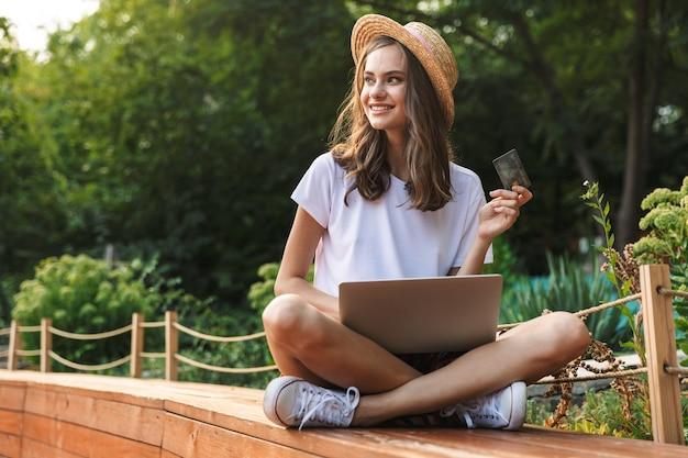 Довольная молодая девушка сидит с портативным компьютером в парке на открытом воздухе, держа кредитную карту