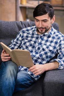 家で時間を楽しみながら本を読んで喜んで若い男