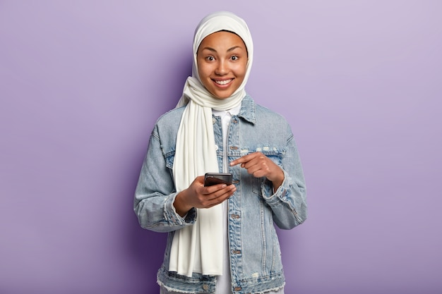그녀의 전화와 함께 포즈를 취하는 기쁘게 젊은 무슬림 여성