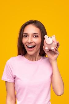 Довольная молодая женщина в розовой футболке смотрит в камеру с открытым ртом и демонстрирует копилку на желтом фоне