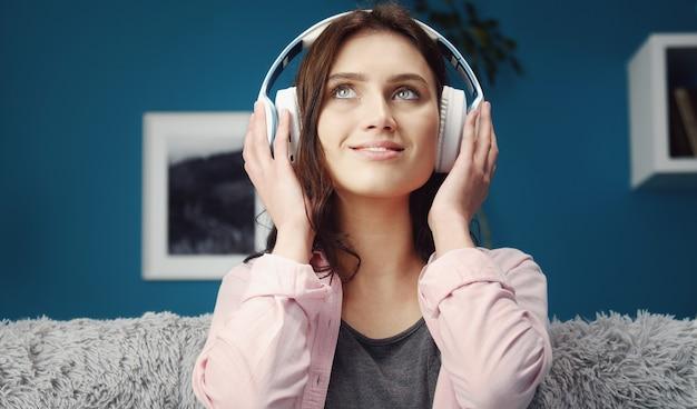 Довольная молодая женщина нажимает гарнитуру руками, глядя вверх, слушая музыку, вид спереди