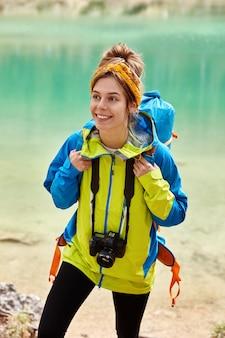 Довольная молодая туристка причесалась, носит шарф на голове, красочный анорак, держит фотоаппарат