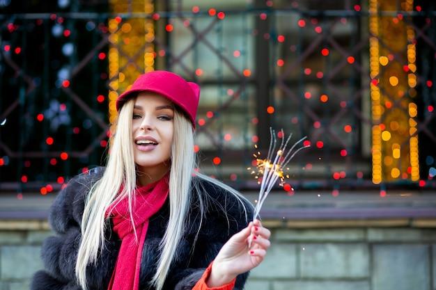 ぼやけた街の明かりで線香花火で新年を祝う楽しい金髪モデル。テキスト用のスペース