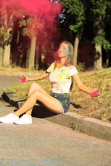 ピンクのホーリーペイントを投げる楽しいブロンドの女性