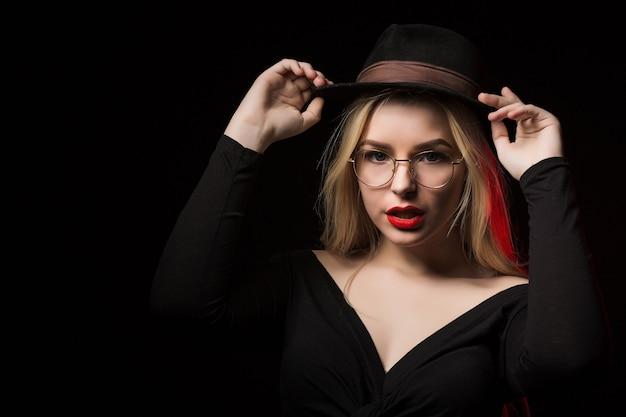 影でポーズをとって、黒いブラウス、帽子、眼鏡を身に着けている楽しいブロンドの女性